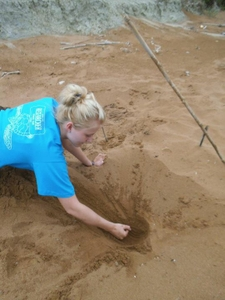 Sophie takes a sand sample for analysis